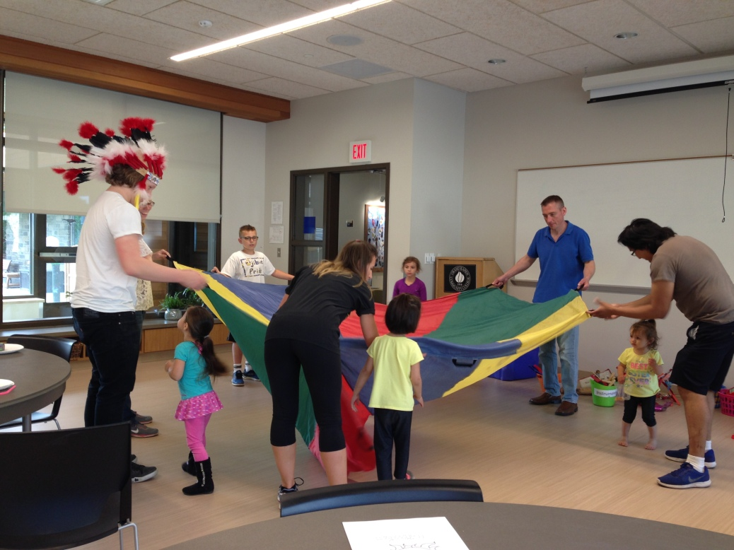 Native American Student Organization members and preschoolers play with a parachute.