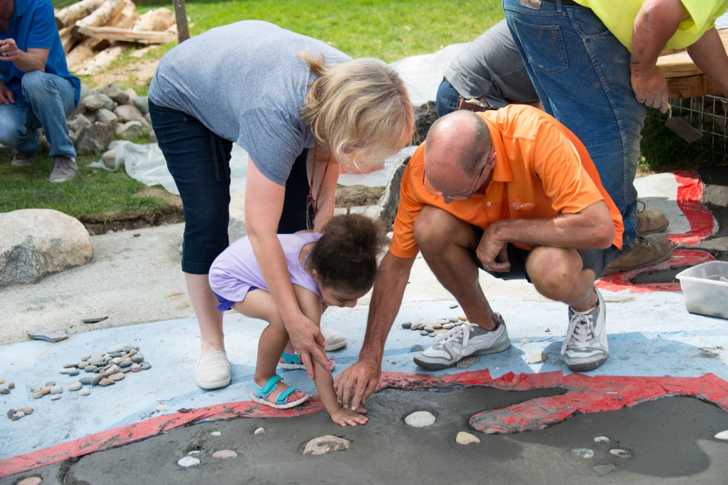A man helps a little girl add a rock to the wet cement of the Michigan map. A woman holds onto the little girl.