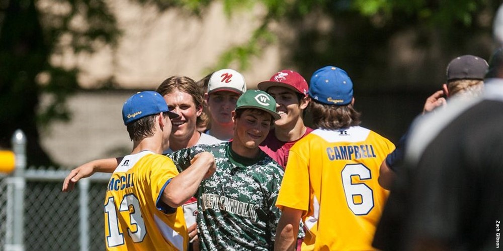 A group of high school baseball players shake hands.