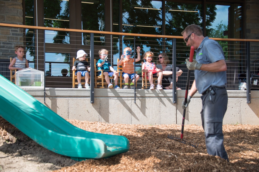 Five preschoolers, seated in rocking chairs, watch a construction worker spread mulch by a slide.