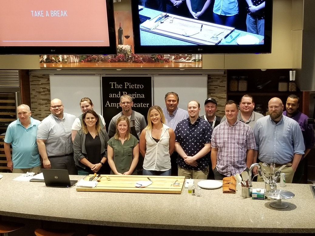 Fourteen alumni from the Secchia Institute for Culinary Education stand behind the counter in the amphitheater