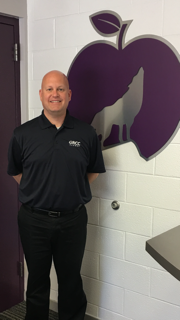 Craig Hoekstra, wearing a GRCC alumni shirt, stands next to a wall painted with the Wyoming school district logo of a wolf in an apple.