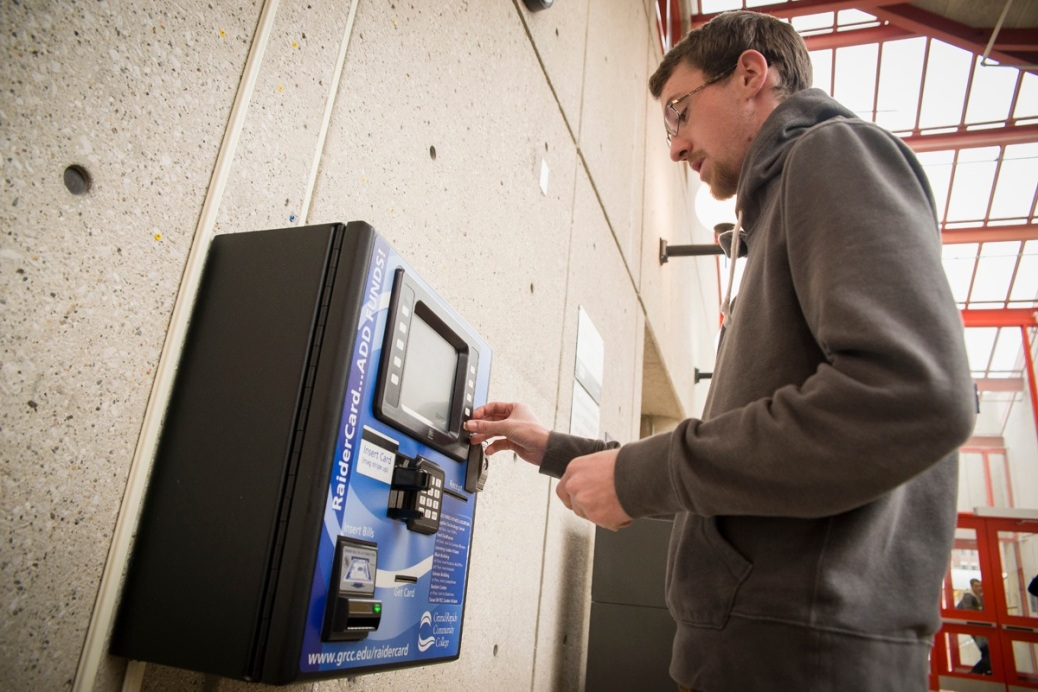 A man uses the wall-mounted machine in the Student Center to put money on his RaiderCard.