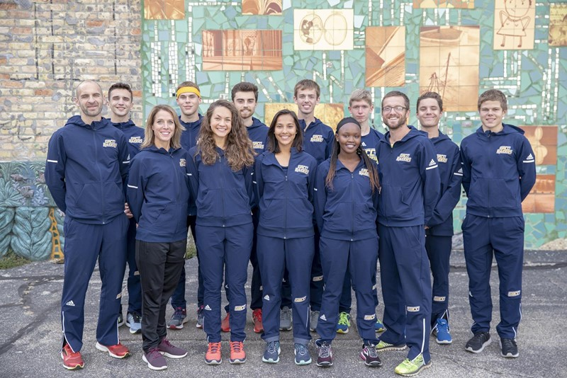 The members of the cross country team stand in front of a mural: assistant coach Dave VanderMeer, Sam Borisch, assistant coach Sharon Becker, Joel Wilson, Hannah Jefferis, Trystan Thayer, Supriya Poelman, Matthew Spees, Edith Jesang, Leo Walquist, head coach Matt Sicilia, Dallas Mora and Dighton Hekman.