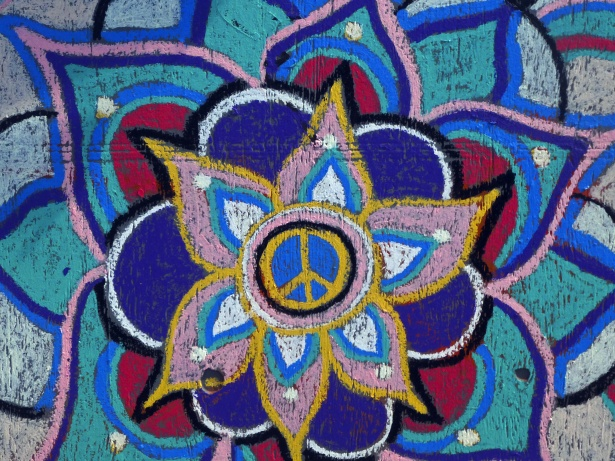 A peace sign is painted in the middle of a flower.