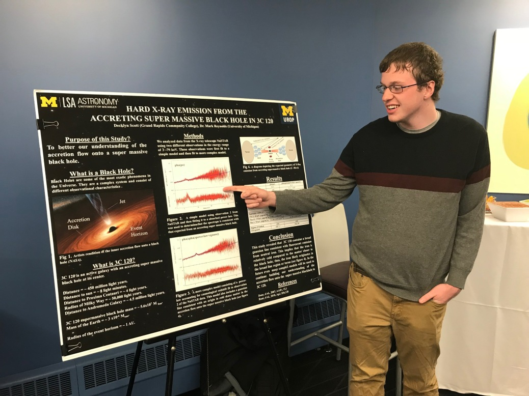 """A student points out information on a posterboard for research he did on the topic """"Hard X-ray Emission frrom the Accreting Super Massive Black Hole in 3C 120."""""""