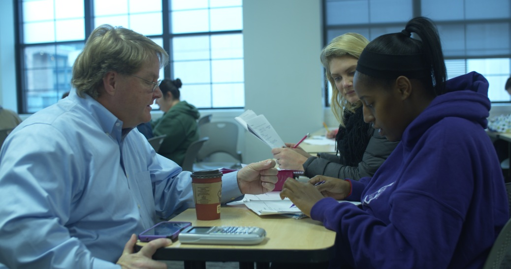 Jeff Spoelman talks to two students seated at a table.