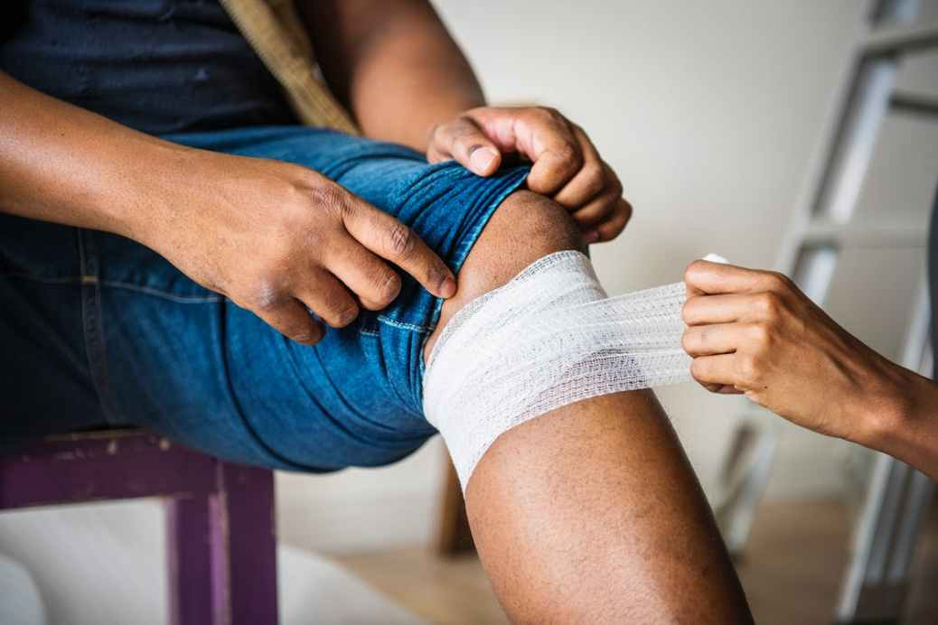 A person gets their knee bandaged up.
