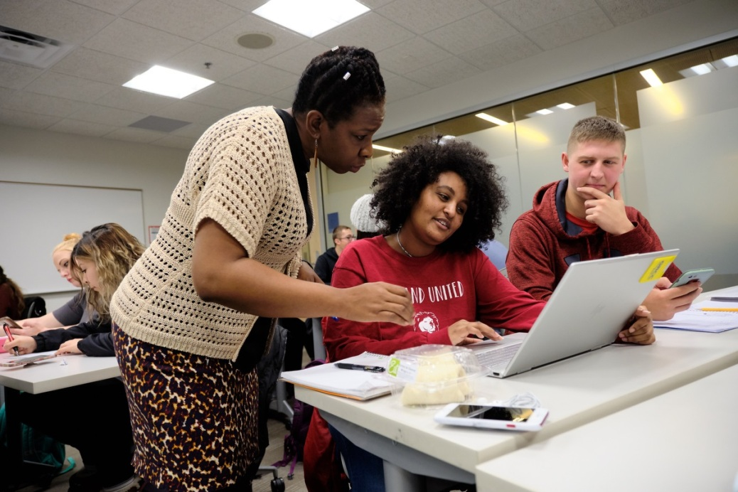 Professor Daisy Henderson looks at something on a students laptop during a sociology class.
