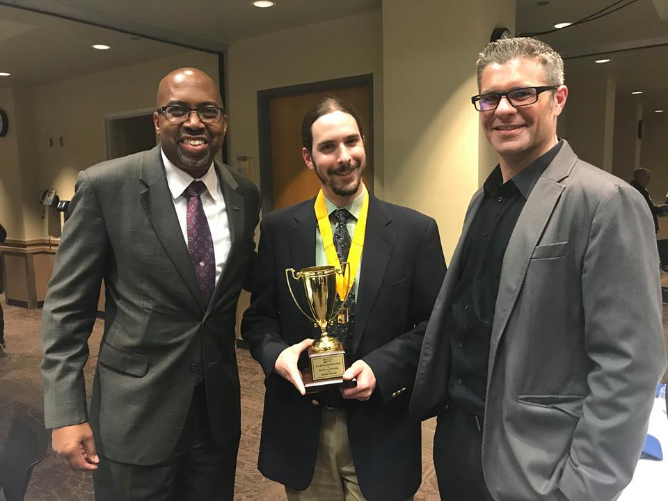 President Pink and Andrew Rozema stand with Daniel Cruzan, who holds his Arthur Andrews Award and wears his Delta Pi Alpha medallion.