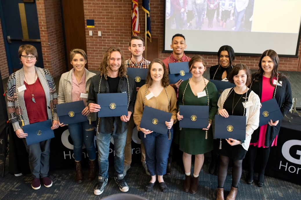 Ten students, all wearing Honors Program cords around their necks, hold up certificates.
