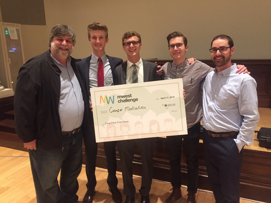 GRCC professor Felix Pereiro stands with Aiden Wysocki, Jake Dabkowski, Matthew Veenhoven and Jonathan Moroney, who hold up a giant check.