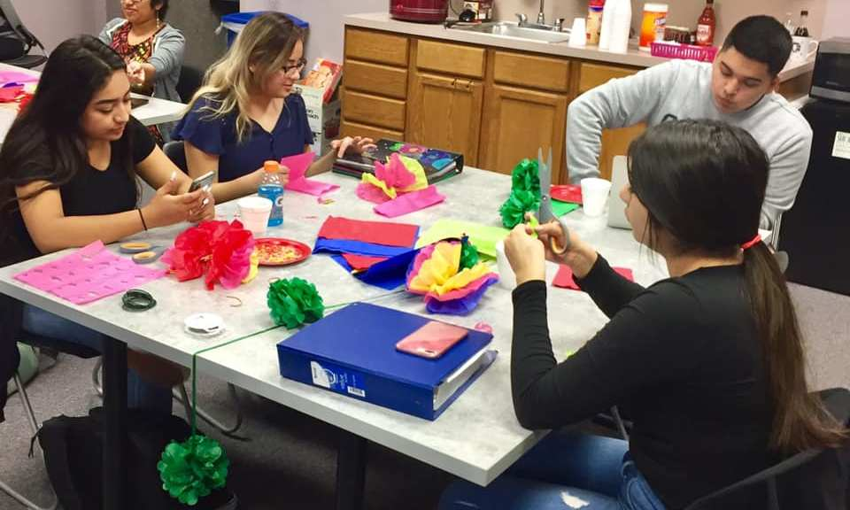 Students make paper flowers.