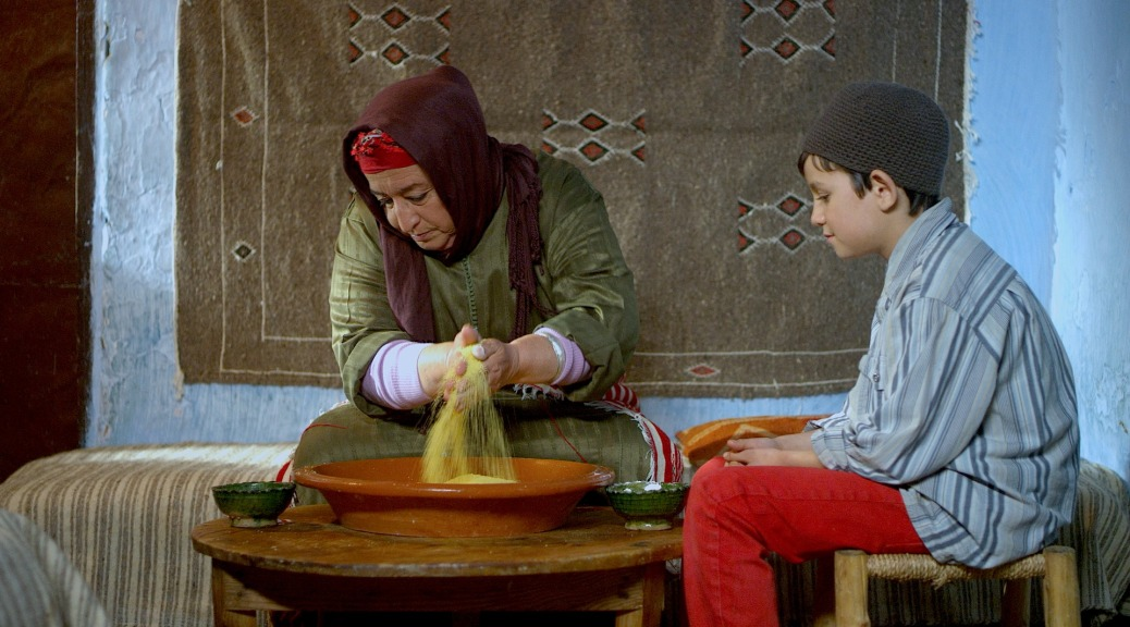 """In a scene from """"Tazzeka,"""" a boy watches a woman mix grain in a bowl."""