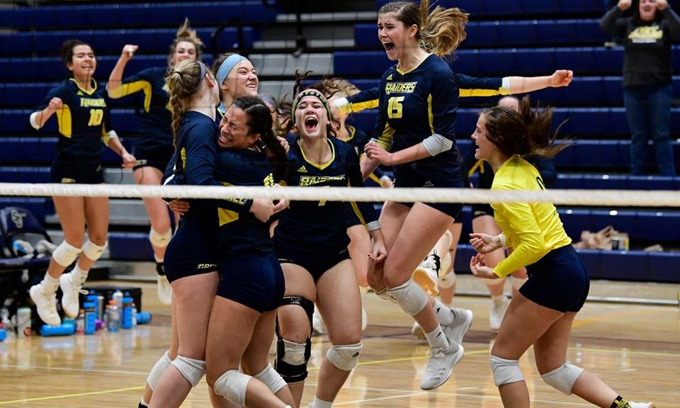 Volleyball players jump up and down and hug on the court.