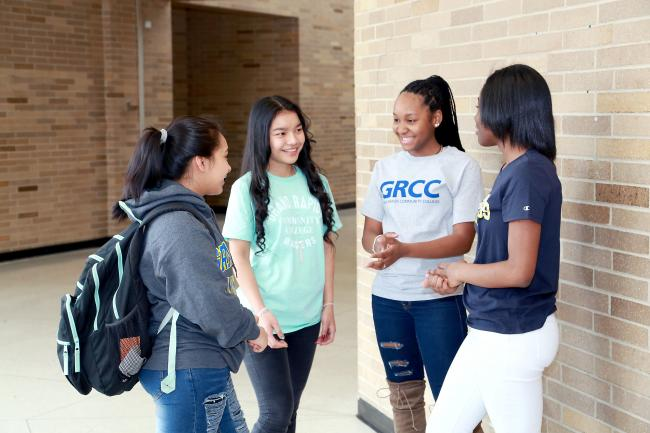 Four students in Ottawa Hills High School's early middle college talk in a hallway.